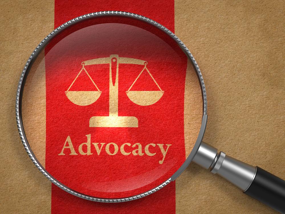 Advocacy Concept Magnifying Glass with Word Advocacy and Icon of Scales in Balance on Old Paper with Red Vertical Line Background.