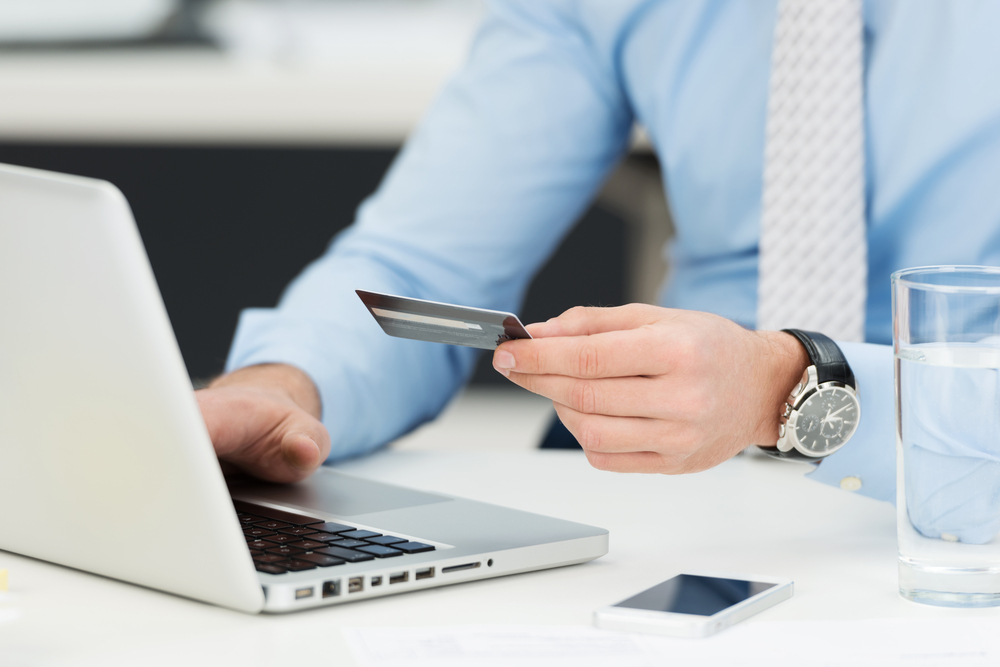 Businessman doing online banking, making a payment or purchasing goods on the internet entering his credit card details on a laptop, close up view of his hands-1