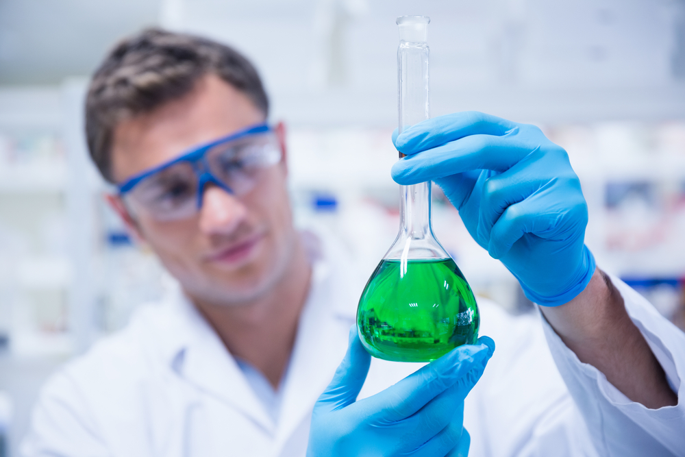 Chemist holding up beaker of green chemical in the laboratory