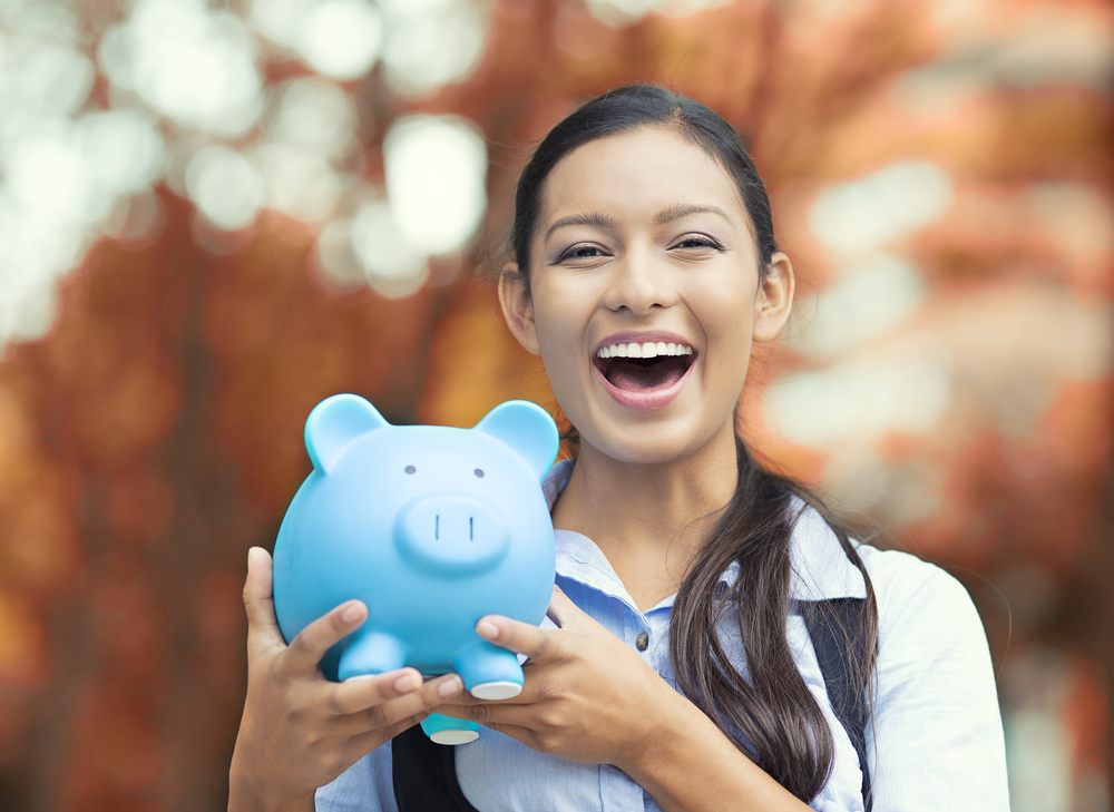 Closeup portrait happy, smiling business woman, bank employee holding piggy bank, isolated outdoors indian autumn background. Financial savings, banking concept. Positive emotions, face expressions-2