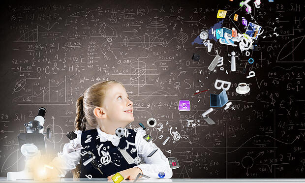 Cute girl of school age using microscope. Technology concept