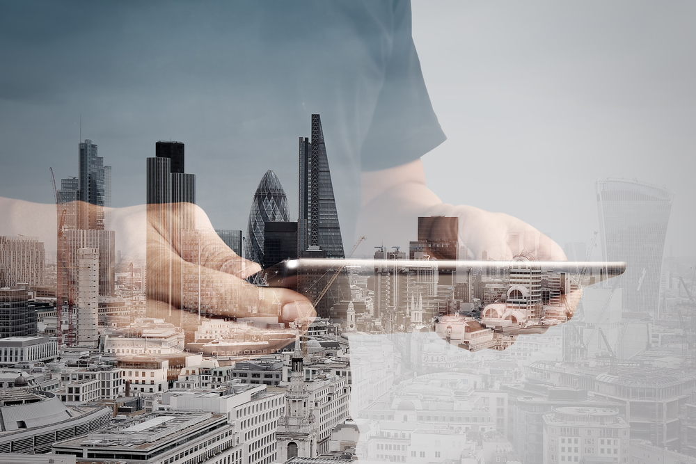 Double exposure of success businessman using digital tablet with london building and social media diagram-1