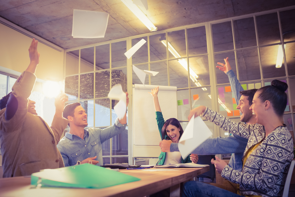 Group of business people celebrating by throwing their business papers in the air-1