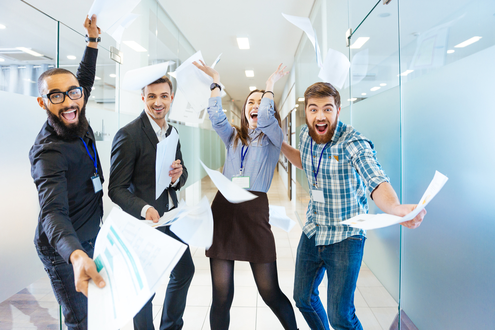 Group of joyful excited business people throwing papers and having fun in office-2