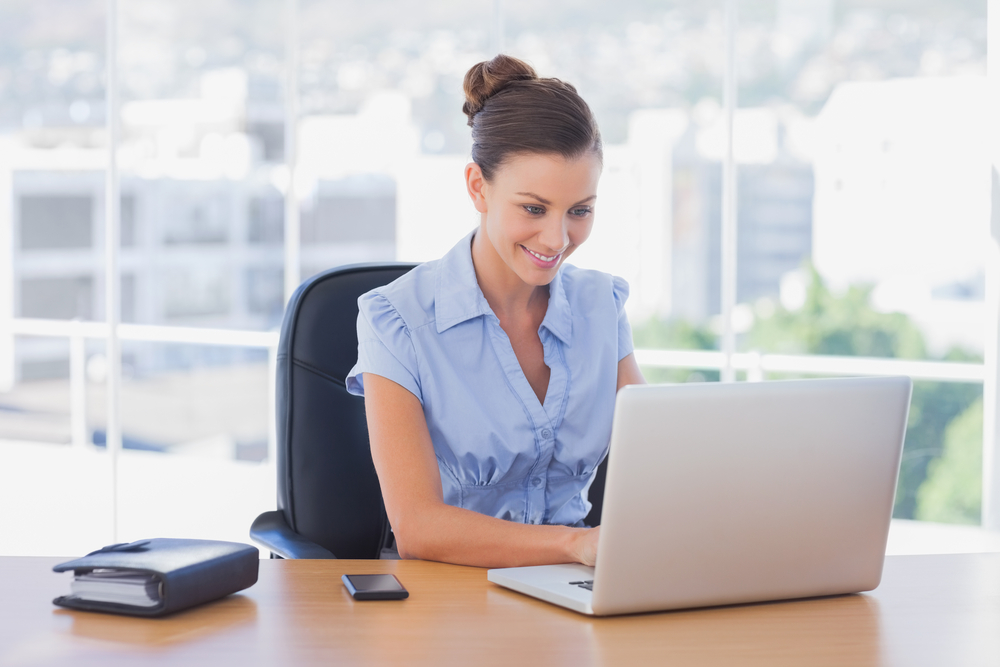 Happy businesswoman working on her laptop in the office