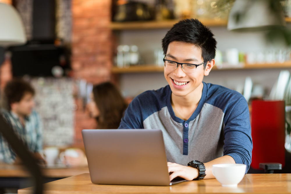 Happy cheerful young asian male in glasses smiling and using laptop in cafe