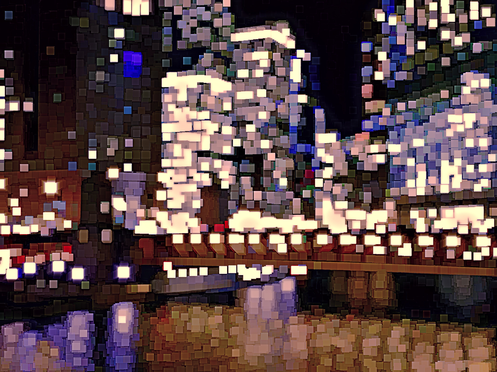 Multicolored abstract of city lights -- all small, solid squares -- with reflections of river below skyscrapers at night