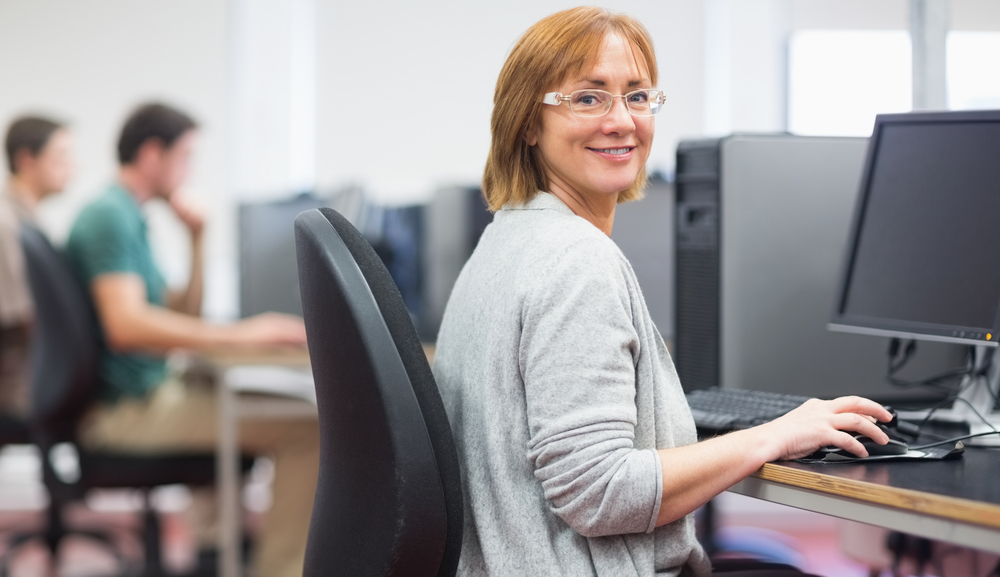 Portrait of a smiling woman by other mature students using computers in the computer room
