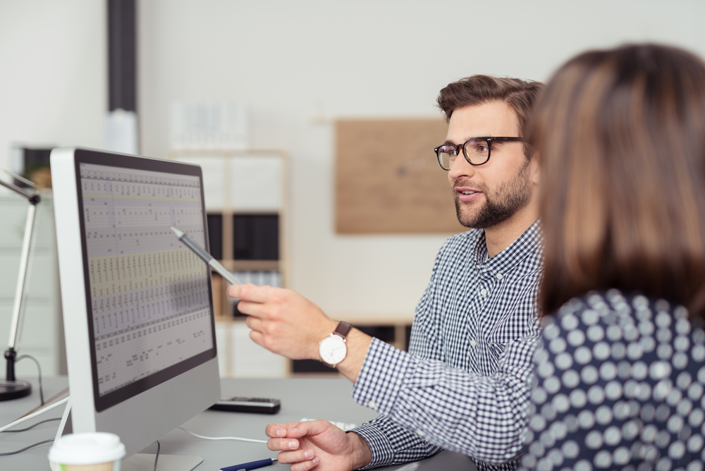 Proficient young male employee with eyeglasses and checkered shirt, explaining a business analysis displayed on the monitor of a desktop PC to his female colleague, in the interior of a modern office-4