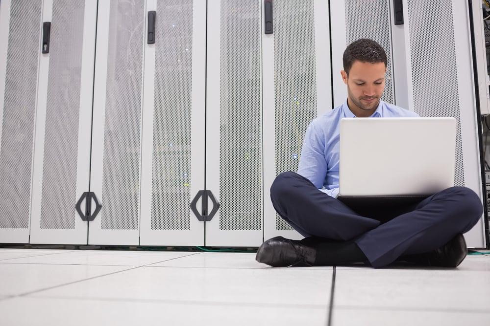 Technician sitting on floor working on laptop in data center-2