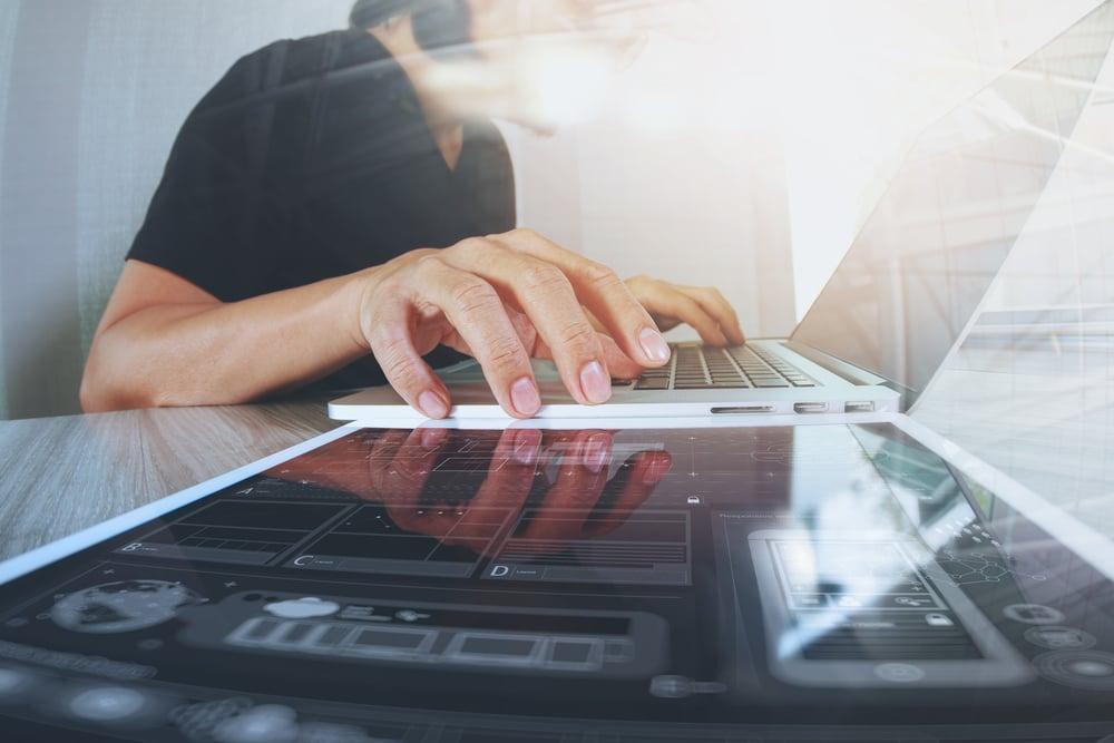 Website designer working digital tablet and computer laptop with smart phone and digital design diagram on wooden desk as concept-1