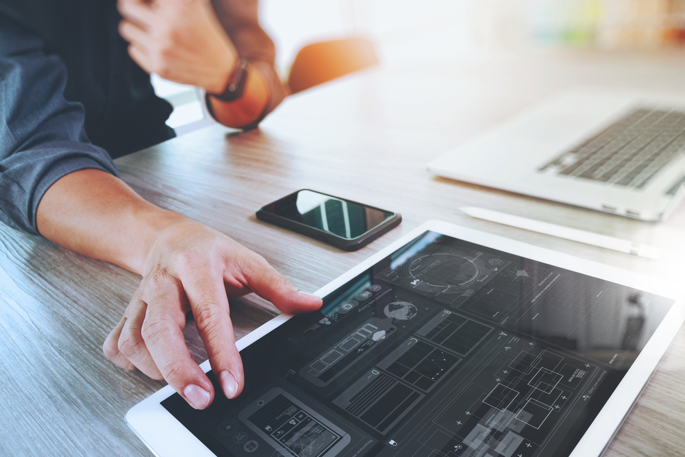 Website designer working digital tablet and computer laptop with smart phone and graphics design diagram on wooden desk as concept-3