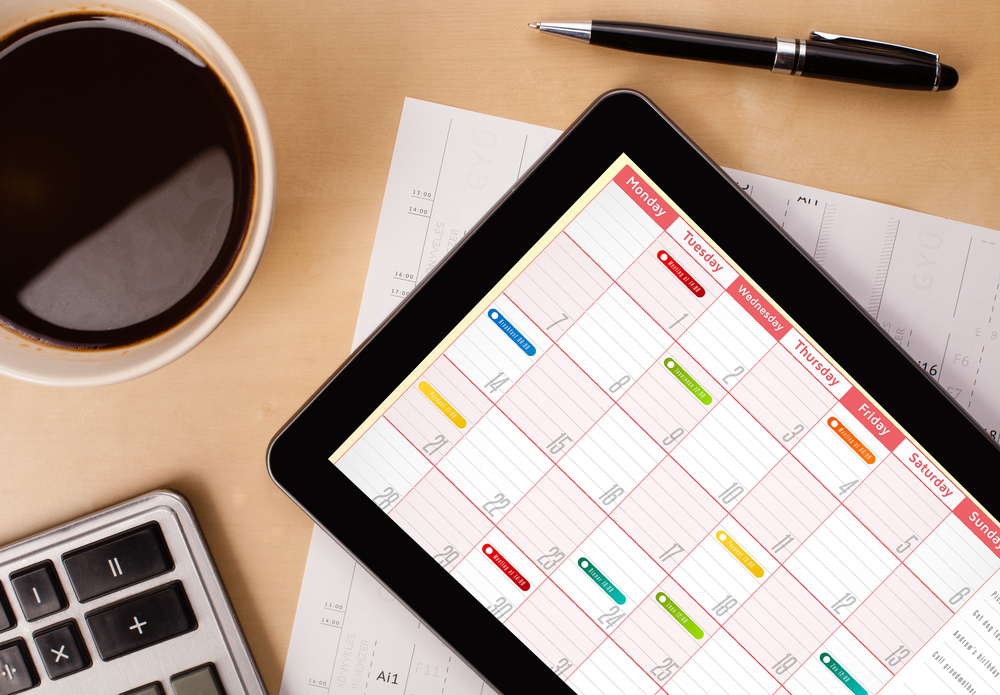 Workplace with tablet pc showing calendar and a cup of coffee on a wooden work table close-up-2