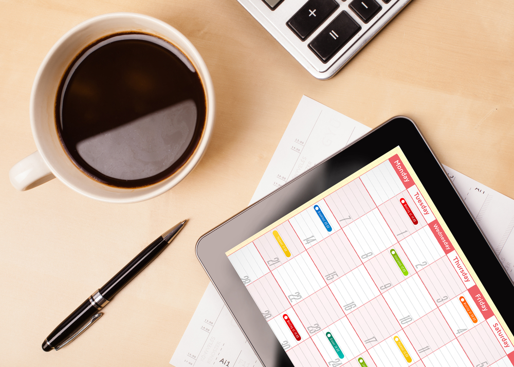 Workplace with tablet pc showing calendar and a cup of coffee on a wooden work table close-up-3