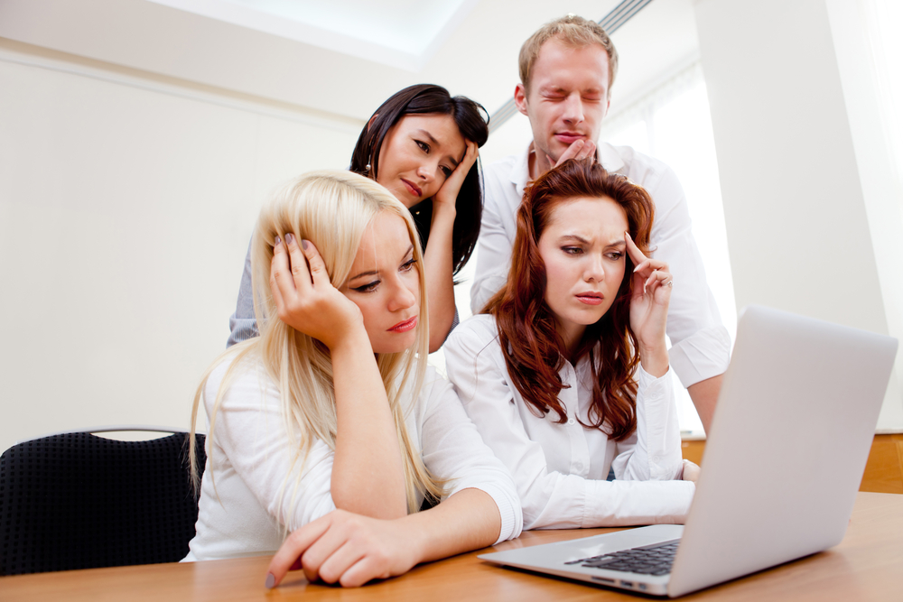 Worried business group going online on a laptop at the office