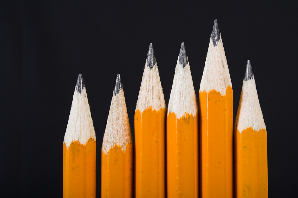 black pencils standing out from the crowd over a black background