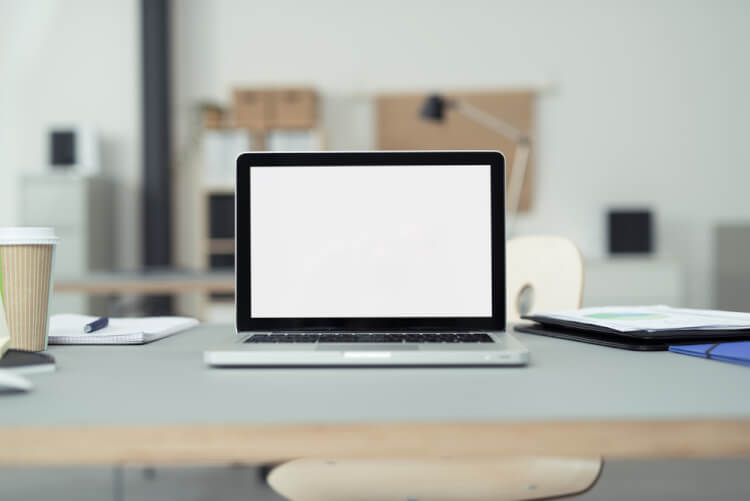 Close up Laptop Computer on Top of Office Table of a Businessman with Empty White Screen, Emphasizing Copy Space.