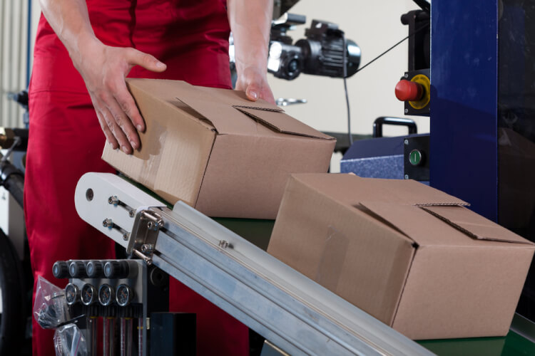 Close-up of worker putting a box on conveyor belt for shipping