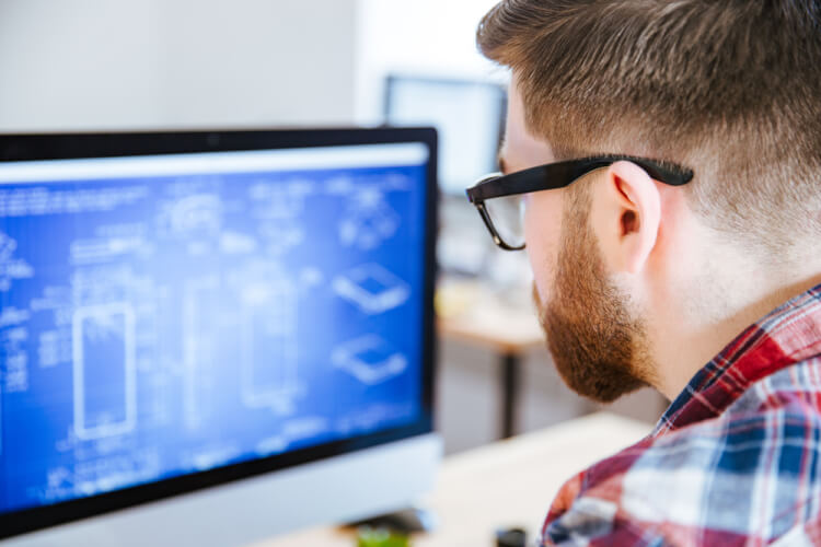 Closeup of young man in glasses with beard making blueprints on computer-1