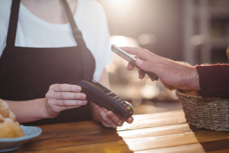 Customer paying bill through smartphone using NFC technology in cafe