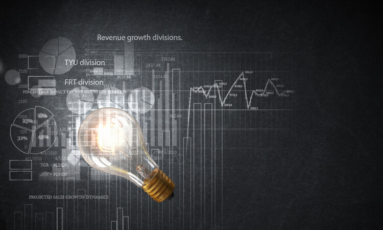 Glowing glass light bulb hanging from above and business sketches at dark background