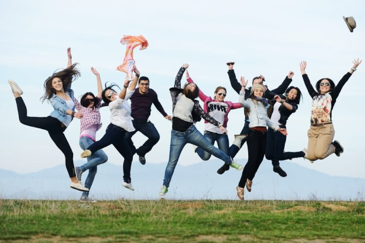 Happy teen girls having good fun time outdoors jumping up in air