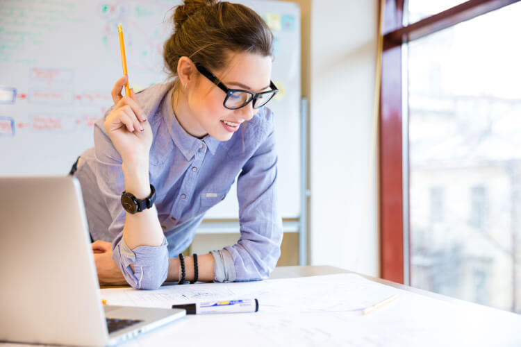 Happy young woman in glasses standing near the window in office and working with blueprint