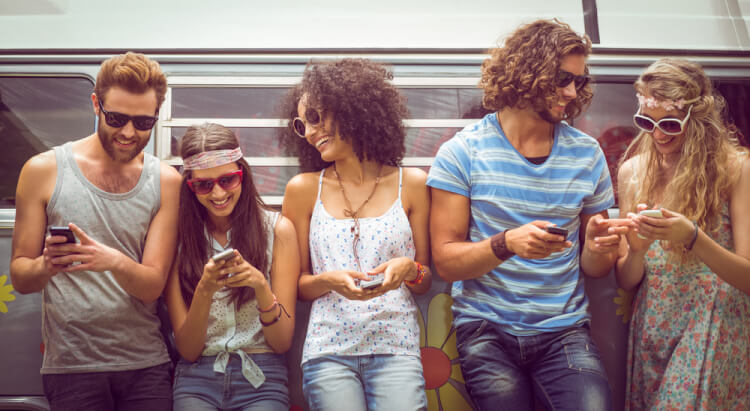 Hipster friends using their phones on a summers day-1