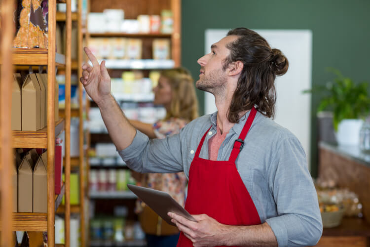 Male staff holding a digital tablet and checking grocery products on the shelf in supermarket-1