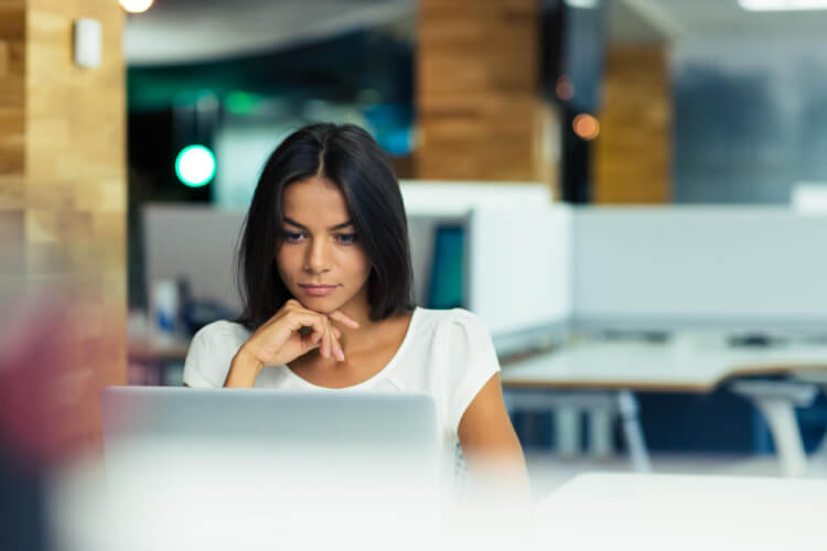 Portrait of a serious businesswoman using laptop in office