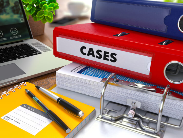 Red Ring Binder with Inscription Cases on Background of Working Table with Office Supplies, Laptop, Reports. Toned Illustration. Business Concept on Blurred Background.