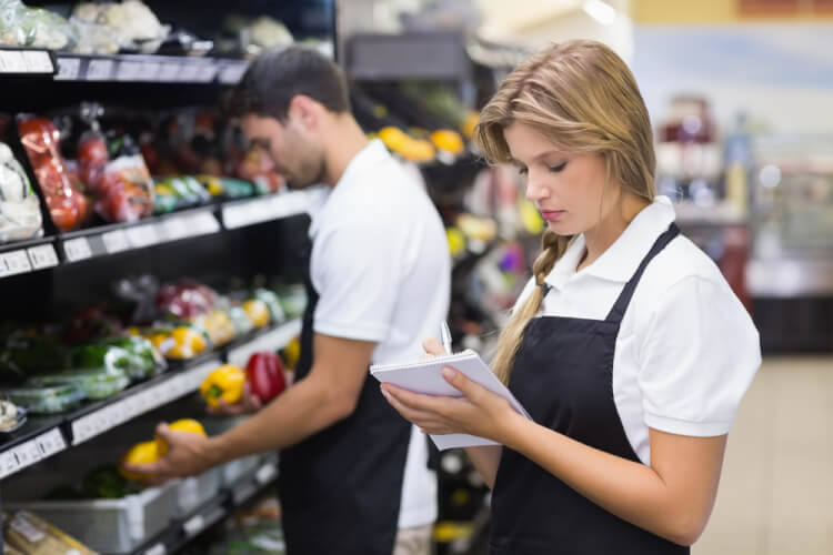 Serious staff woman wrting on notepad at supermarket