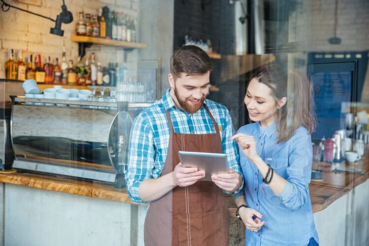 Smiling handsome waiter holding tablet and young pretty woman pointing on it in coffee shop-1