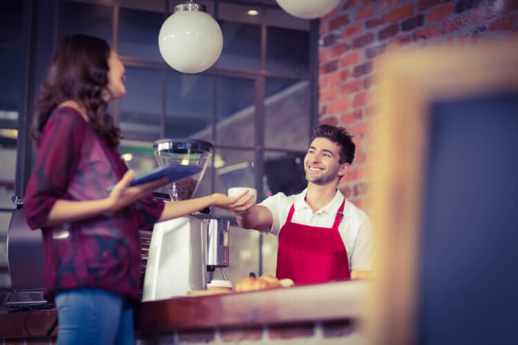 Smiling waiter serving a client at the coffee shop