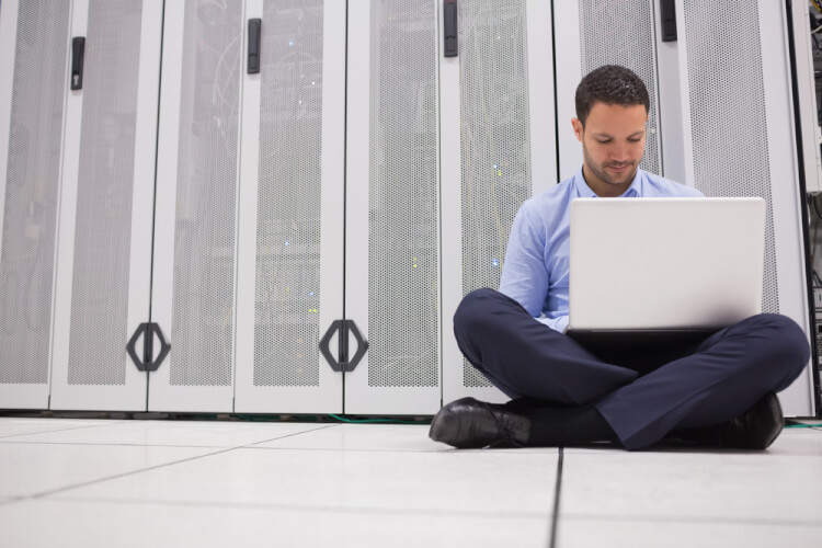 Technician sitting on floor working on laptop in data center-1
