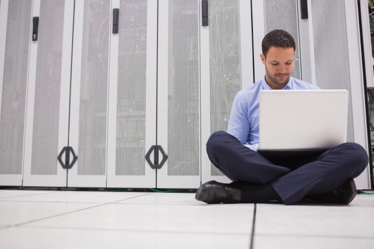 Technician sitting on floor working on laptop in data center