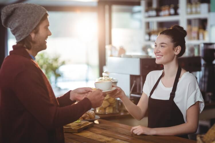 Waitress serving a cup of coffee to customer in cafe