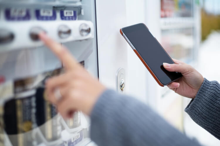 Woman use of soft drink vending system paying by cellphone