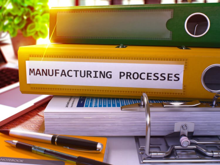 Yellow Ring Binder with Inscription Manufacturing Processes on Background of Working Table with Office Supplies and Laptop. Manufacturing Processes Concept on Blurred Background. 3D Render.