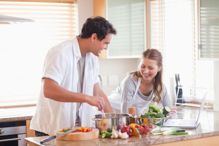 Young couple using the internet to look up recipe