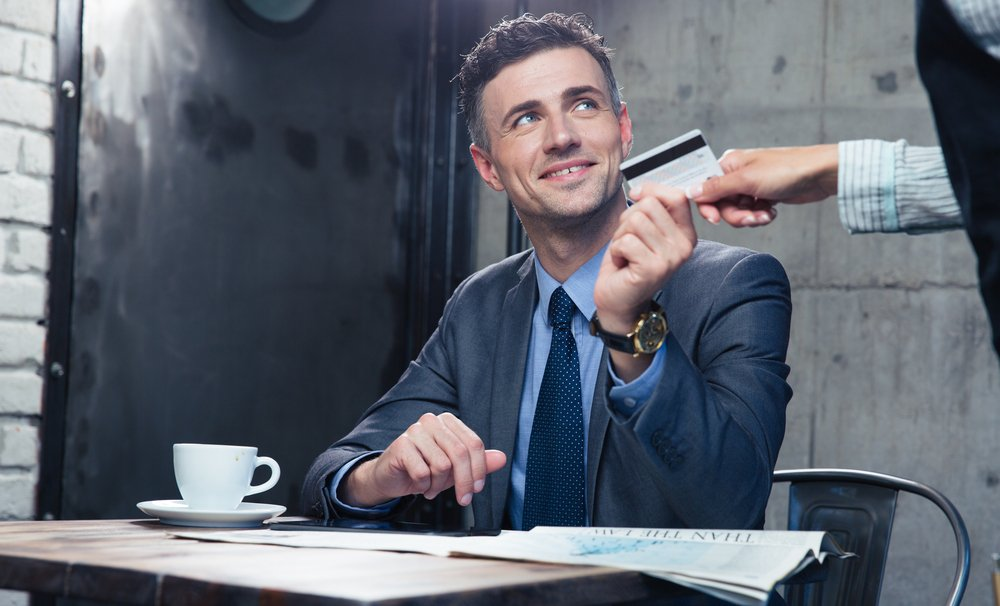 Happy businessman passing his credit card to waiter in cafe