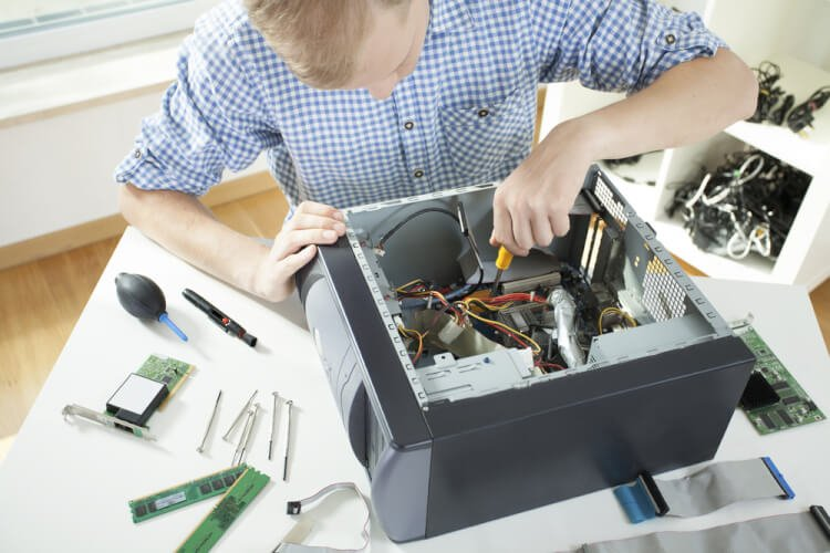 Young man fixing computer on his own